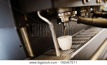 Espresso coffee made by barista and machine