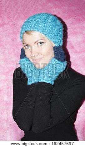 Portrait of a girl in blue knitted cap and mittens kroplin up on a pink background. Smiling snow maiden