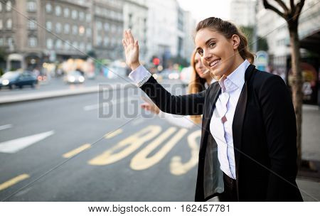 Business cute women hailing taxi on street