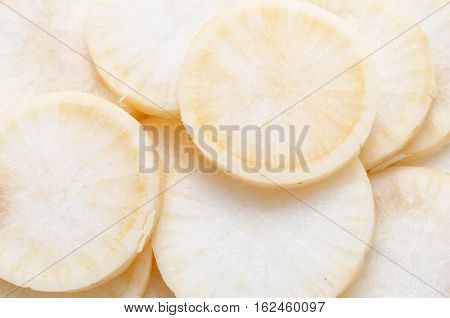 vegetable daikon sliced on a wooden cutting board close up