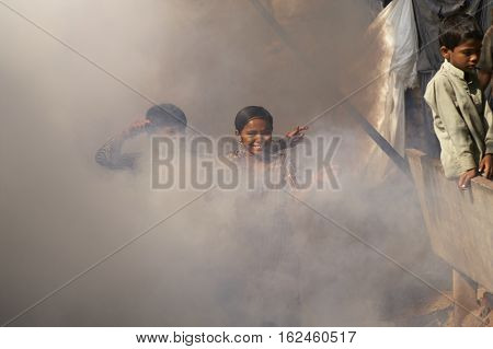 AHMADABAD, INDIA - OCTOBER 31, 2007: Children playing in a cloud of insecticide powder being sprayed amongst the dwellings of a shanty town in Ahmadabad, Gujarat, India.