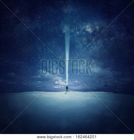 Milky Way night sky with stars and silhouette of a standing alone man in the middle of a sandy desert pointing up the lantern light trying to find a specific star.