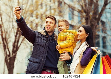 Happy family doing selfi after shopping outdoor