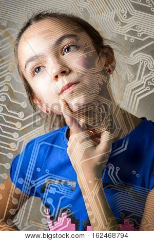 11 year old girl looks thoughtfully through the silhouette of a computer motherboard leaning a finger to her cheek. the concept of a new technological generation of college information technology.