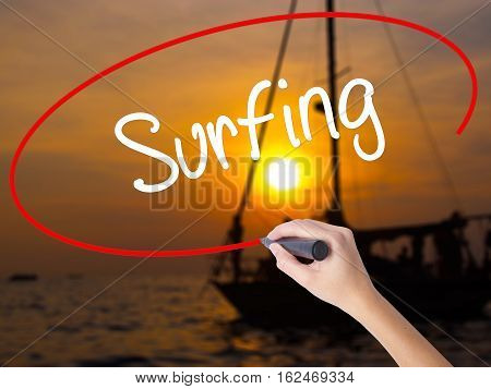 Woman Hand Writing Surfing  With A Marker Over Transparent Board