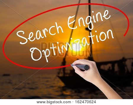 Woman Hand Writing Search Engine Optimization With A Marker Over Transparent Board