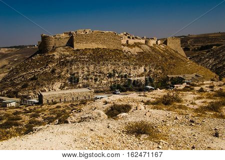 Photo of the Remains ancient impressive castle on mountain. Shobak crusader fortress. Castle walls. Travel concept. Jordan architecture and attraction