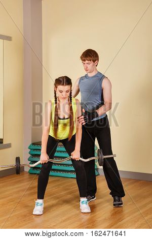 Coach man oversees the exercises with barbell girl. Personal coach. Healthy lifestyle concept. Fitness.