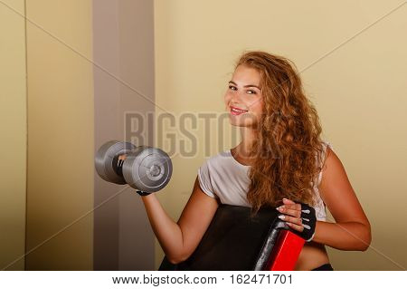Lovely girl doing exercise for biceps with hand weights. Working with free weight. Healthy lifestyle concept. Fitness.