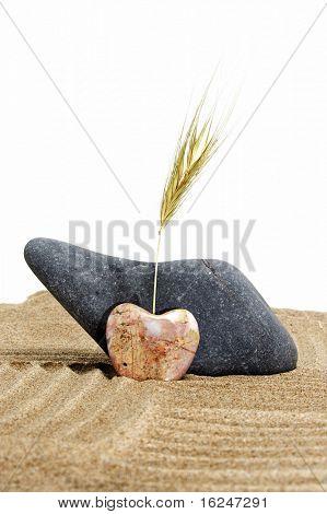 zen stones, one heart shapped, on a zen garden in a white background