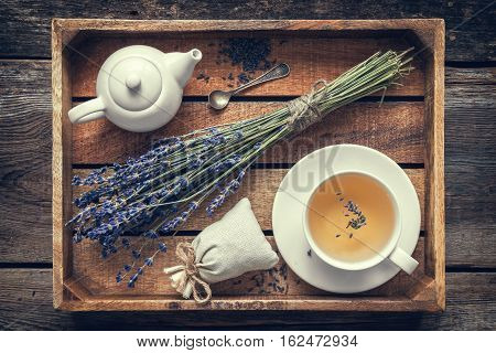 Bunch Of Lavender Flowers, Healthy Tea In Cup, Teapot And Sachets Filled With Dried Lavender In Wood