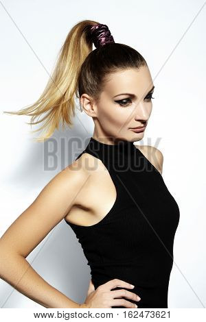 Fashion portrait of beautiful young woman with ponytail hairstyle. Beauty shot of sexy girl on white background. Pony tail straight hair catwalk black eyeliner makeup on model face