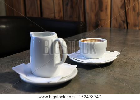 Cup Of Cappuccino And Jug Of Milk On Wooden Background.