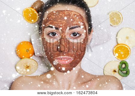 winter christmas people beauty concept- Natural homemade fruit facial masks. Fresh fruit. close-up portrait. beautiful brunette girl with no makeup natural makeup over snow background