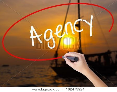 Woman Hand Writing Agency With A Marker Over Transparent Board