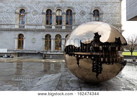 DUBLIN IRELAND - FEB 15 2014: Abstract spherical metal sculpture on a courtyard of Trinity College. The college is the oldest University of Ireland.