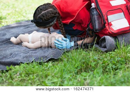 First aid training. Paramedic demonstrate Cardiopulmonary resuscitation (CPR) on baby dummy.