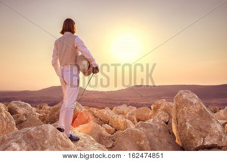 Fencer Man Holding Sword On Top Of The Rock