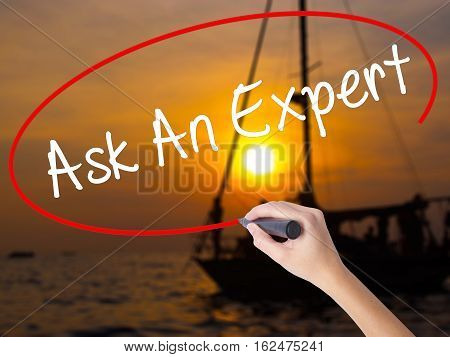 Woman Hand Writing Ask An Expert With A Marker Over Transparent Board