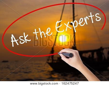 Woman Hand Writing Ask The Experts With A Marker Over Transparent Board