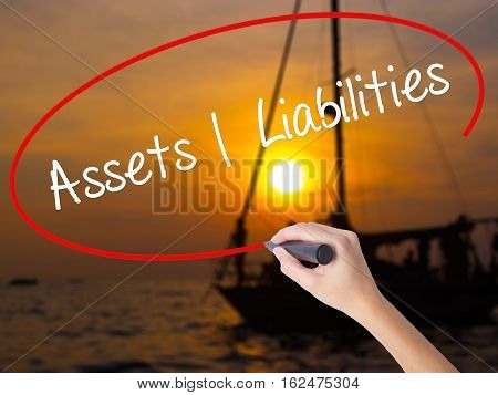 Woman Hand Writing Assets Liabilities With A Marker Over Transparent Board