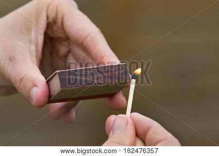 hands striking a match on blurred background