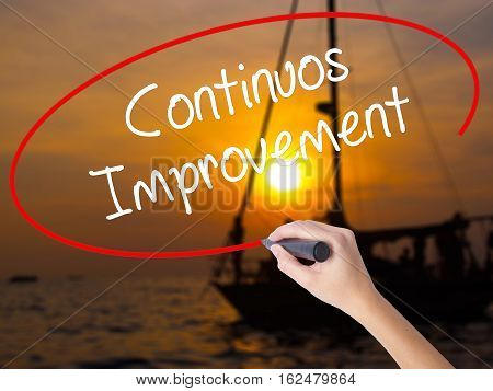 Woman Hand Writing Continuos Improvement With A Marker Over Transparent Board