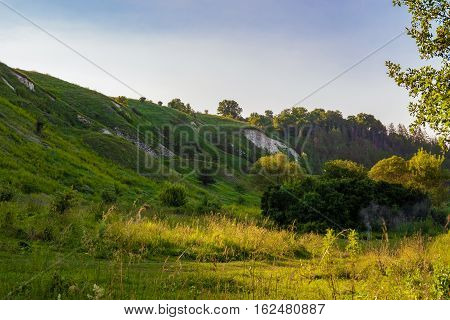 Green chalk hills under a cloudy sky. The multilayered archaeological monument - Krapivinskaya settlement Belgorod region Russia.