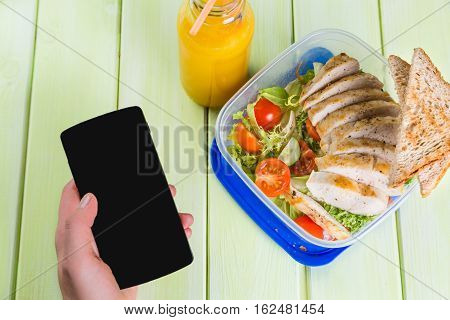 Lunch box with salad and chicken, top view