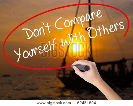 Woman Hand Writing Don't Compare Yourself With Others With A Marker Over Transparent Board
