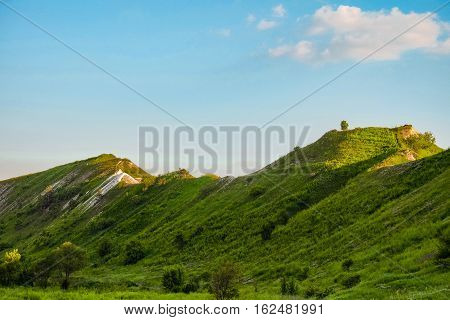 Green chalk hills under blue sky. The archaeological monument - Krapivinskaya settlement Belgorod region Russia.