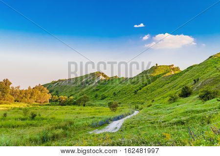 Path at the foot of ridge chalk hills. Green hills under blue sky. The archaeological monument - Krapivinskaya settlement Belgorod region Russia.