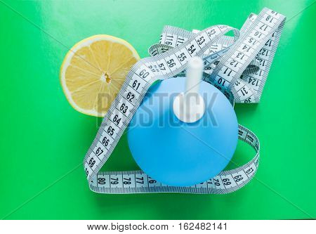 Blue medical enema and fresh lemons measuring tape - diet and medical concept