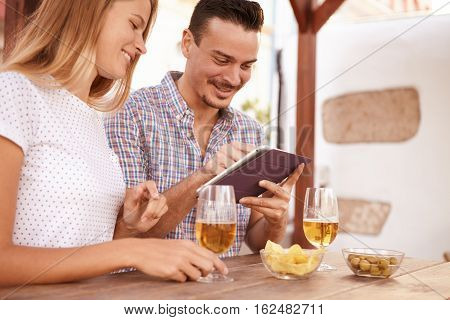 Smiling Couple With Beers And Touchpad