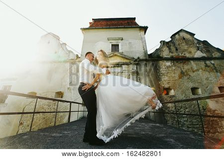 Fiance Dance With A Bride In The Sunshine On An Old Bridge