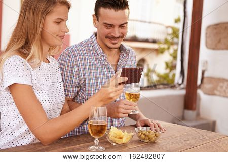 Sweet Couple Looking At Cellphone Satisfied