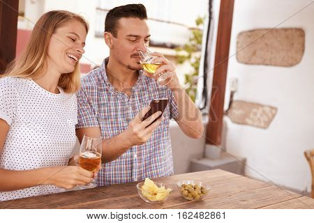 Man Sipping Beer While Sharing Cellphone