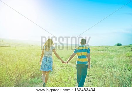 A Young Couple Holding Hands. In Nature Sunset On The Wheat Field Look Forward
