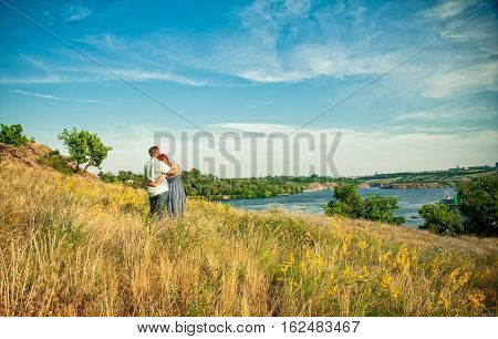Young Man And Woman In A Romantic Place. Couple In Love Outdoors In A Wheat Field Embracing, Looking
