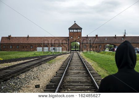 Person standing at Rail entrance to concentration camp at Auschwitz Birkenau KZ Poland