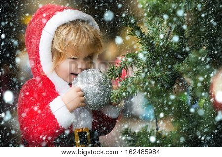 small santa claus cute boy or smiling child in red new year coat with white fur celebrates christmas or xmas holidays near green decorated tree with big balls toys under snow and snowflakes