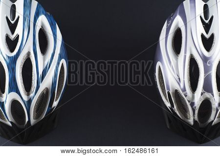 Two bicycle helmet closeup on a black background with copy space. Helmets male and female top view. Stylish sports background.