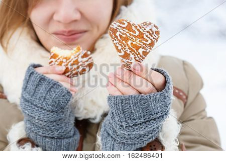 Young Woman In Winter Coat And Knitted Grey Mittens Hold Beautiful Heart Shaped Biscuit Cookies, One