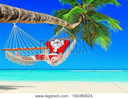 Santa Claus relax tanning in white mesh hammock under coconut palm tree shade at tropical paradise sandy ocean island beach. Happy New Year and Merry Christmas travel destinations concept