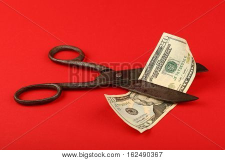 Scissors Cut Us Dollars Over Red Background