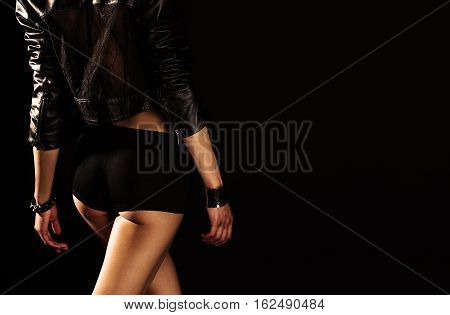Stylish girl in black shorts in black background