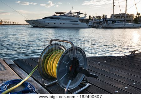 wather hose in marina with yachts and boats on sunset Halkidiki Greece