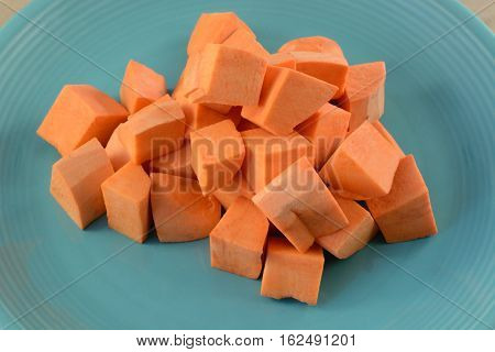 Close up of aw uncooked yam cubes on blue plate