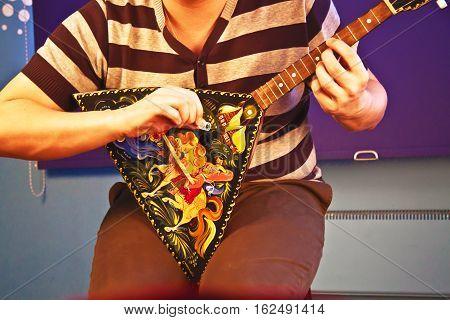 Russian balalaika is the musical instruments. Man playing.