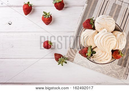 tasty zephyrs on white wooden table. sweet zephyrs and strawberry on wood background.